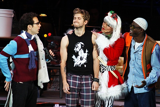 Sharing Christmas Eve on the Lower East Side are Skylar Astin (Mark), Aaron Tveit (Roger), Telly Leung (Angel) and Wayne Brady (Tom Collins) in the Hollywood Bowl production of Rent, directed by Neil Patrick Harris. Photographer: Bruce Glikas, © Broadway.com