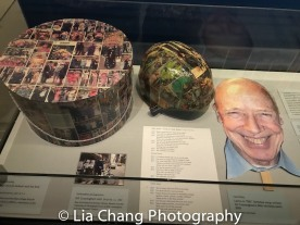 A custom-made bicycle helmet, given to Cunningham in 2005 by Bergdorf Goodman in a hat box covered with colorful images from his New York Times column; Carol Dietz Bill Cunningham mask, made for Cunningham's 80th birthday Party. 2009 Courtesy Carol Dietz. Photo by Lia Chang