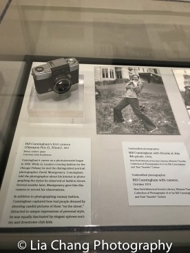 """Bill Cunningham's first camera (Olympus Pen-D 35mm), 1967 Metal, rubber, glass; Bill Cunningham with camera, October 1974. Photo courtesy of the New-York Historical Society Library, Melanie Tinnelly Collection of Photographs of or by Bill Cunningham and Toni """"Suzette"""" Cimino."""