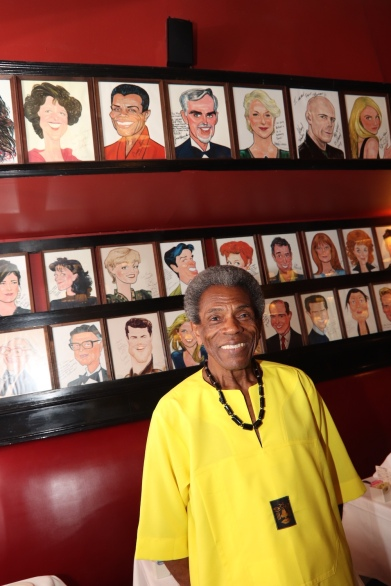 André De Shields underneath his portrait at Sardi's in New York. Photo by Lia Chang