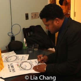 Brandon J. Dirden signs posters. Photo by Lia Chang